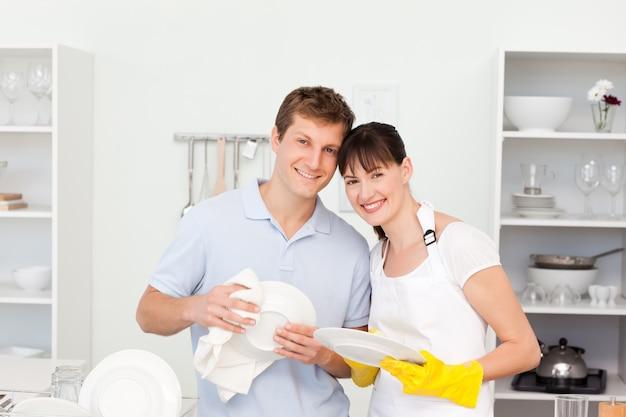 Casal lavando pratos juntos