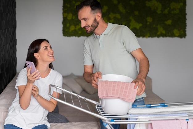 Casal lavando roupa juntos em casa