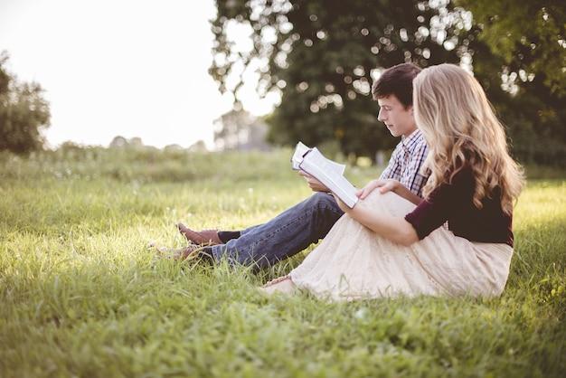 Casal lendo a bíblia juntos em um jardim sob a luz do sol