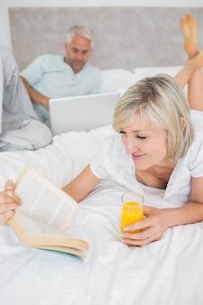 Casal lendo livro e usando o laptop na cama
