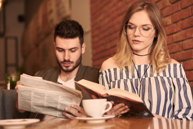 Casal lendo papel e livro
