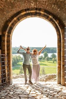 Casal levantando as mãos no ar na frente de uma porta