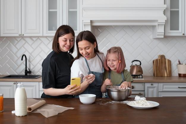 Casal lgbt passando um tempo junto com a filha na cozinha