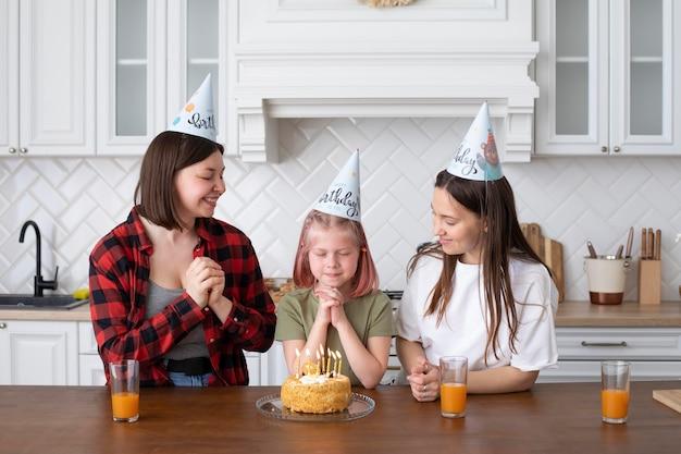 Casal lgbt passando um tempo junto com a filha no aniversário dela