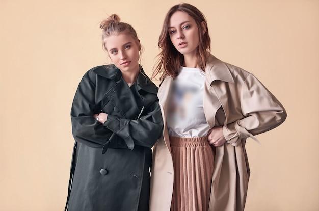 Casal lindas garotas hipster vestindo casacos de moda na rua