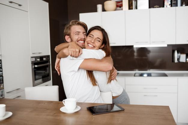 Casal lindo feliz abraçando sorrindo na cozinha de manhã.