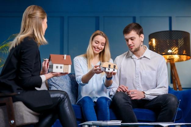 Casal lindo feliz discutindo o projeto da casa com o jovem designer feminino no escritório azul.
