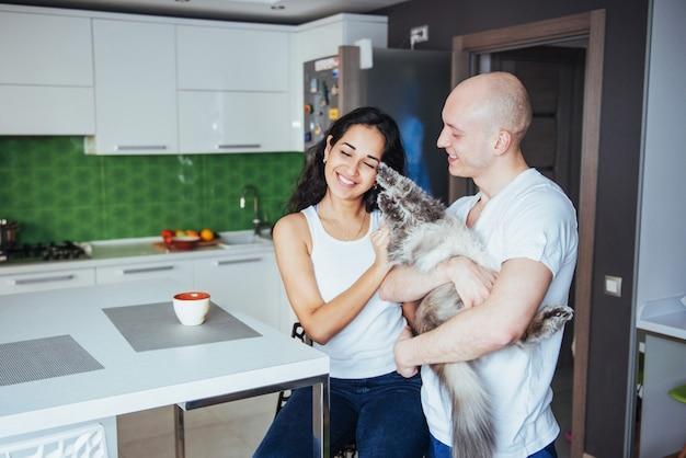 Casal lindo jovem feliz itting na cozinha gato sorrindo.