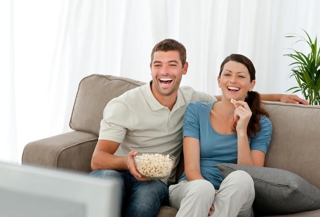 Casal lindo rindo enquanto relaxa na frente da televisão