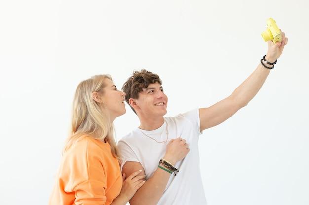 Casal louco engraçado loira e um cara hipster tirando uma selfie em um filme amarelo vintage