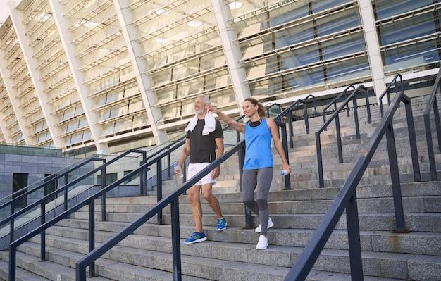 Casal maduro ativo e mulher em roupas esportivas, conversando enquanto desce as escadas