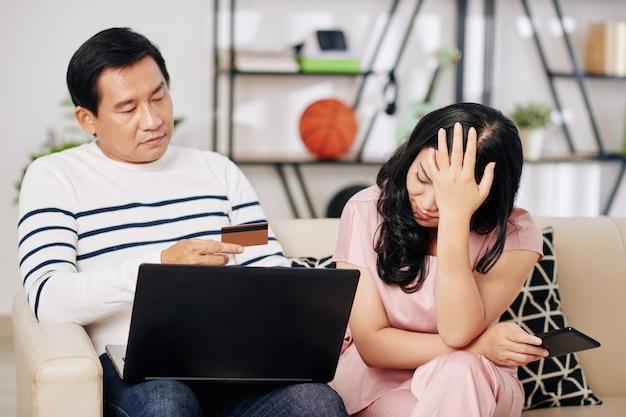 Casal maduro chateado sentado no sofá com laptop e cartão de crédito depois de gastar todo o dinheiro no pagamento de contas