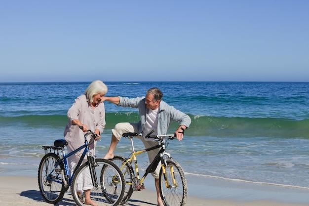 Casal maduro com suas bicicletas na praia