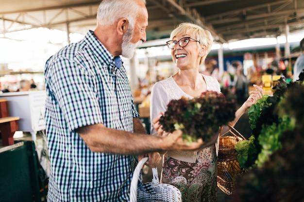 Casal maduro de compras com cesta no mercado. dieta saudável.