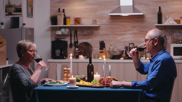Casal maduro de idosos, bebendo uma taça de vinho durante o jantar romântico. idosos tilintando, sentados à mesa da cozinha, apreciando a refeição, comemorando seu aniversário na sala de jantar.