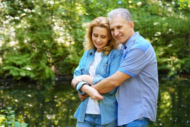 Casal maduro e feliz fica na floresta em um dia ensolarado e abraço. o conceito de relacionamentos familiares felizes
