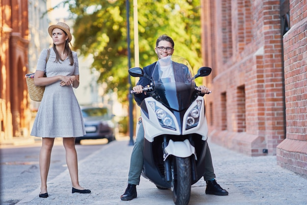 Casal maduro feliz andando de scooter na cidade em um dia ensolarado