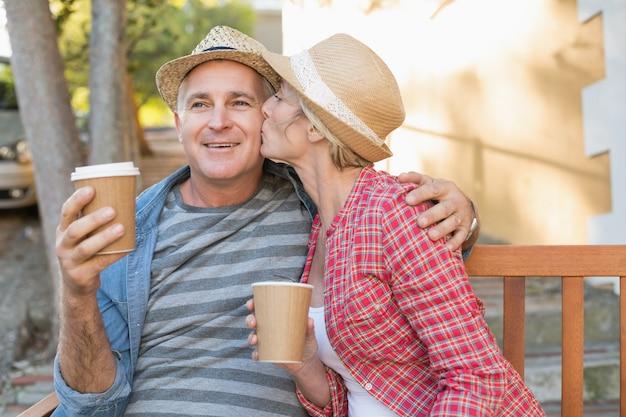 Casal maduro feliz bebendo café em um banco na cidade