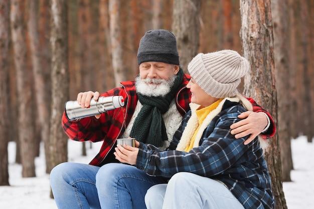 Casal maduro feliz bebendo chá quente na floresta no dia de inverno