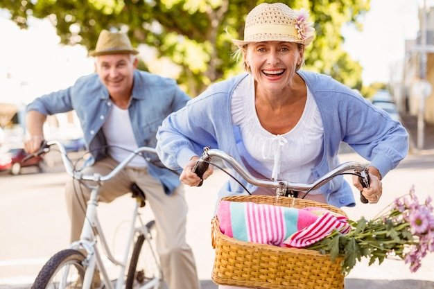 Casal maduro feliz indo para um passeio de bicicleta na cidade