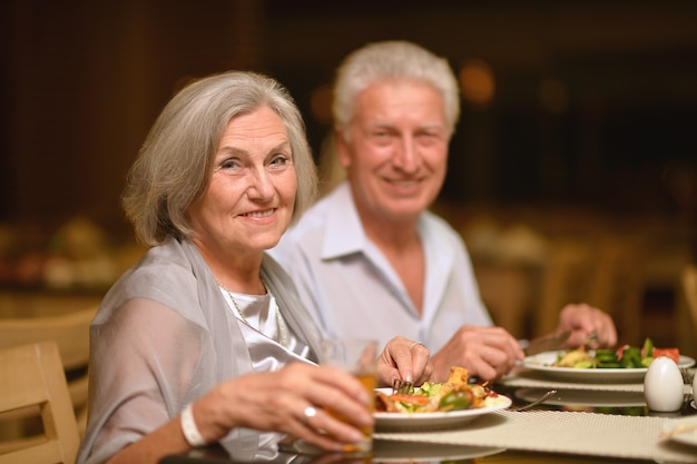 Casal maduro feliz jantando em restaurante