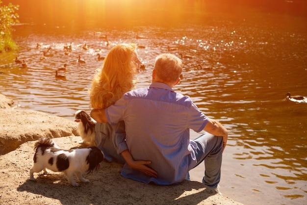 Casal maduro feliz sentado no lago ao sol com seus cães. conceito de férias em família na natureza