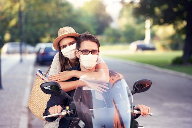 Casal maduro feliz usando máscaras enquanto dirigia uma scooter na cidade em um dia ensolarado