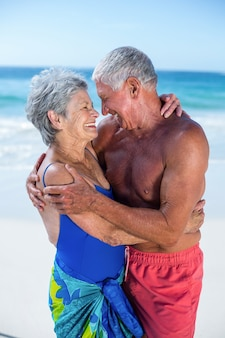 Casal maduro fofo se abraçando na praia