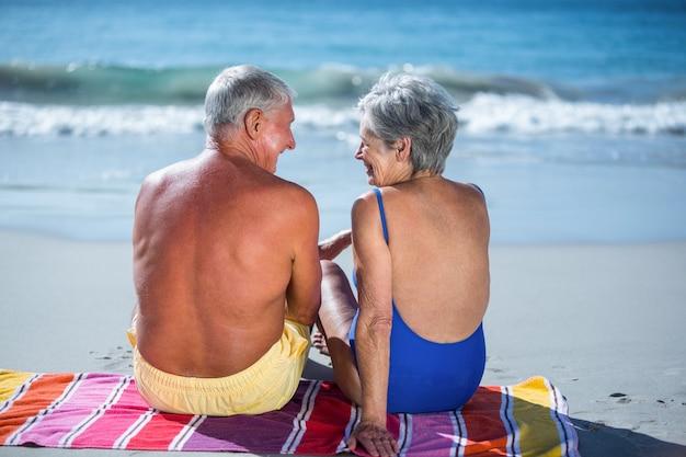 Casal maduro fofo sentado em uma toalha na praia
