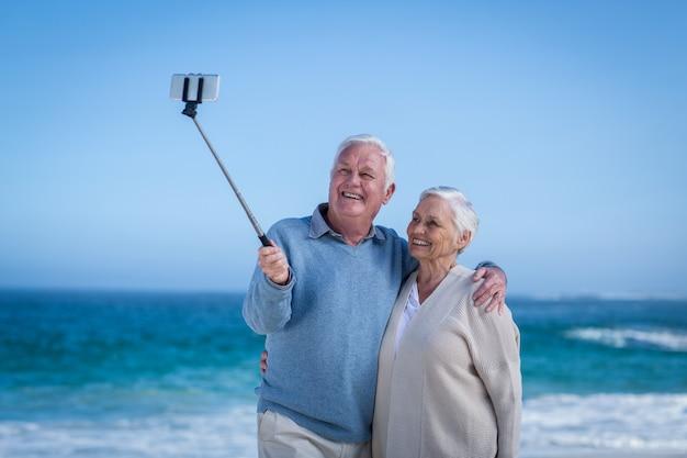 Casal maduro fofo tirando selfie com bastão de selfie