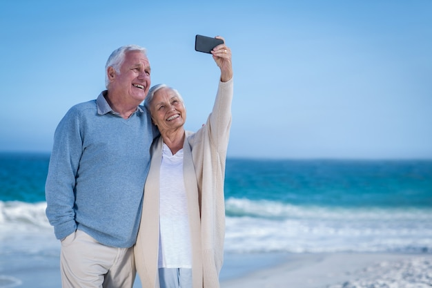 Casal maduro fofo tirando selfie na praia