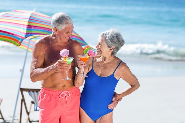 Casal maduro fofo tomando coquetéis na praia