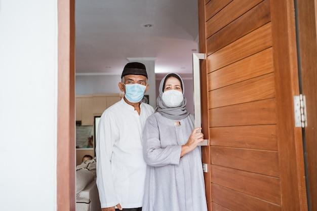 Casal maduro muçulmano usando máscara facial em pé na porta da frente de sua casa com um gesto de saudação
