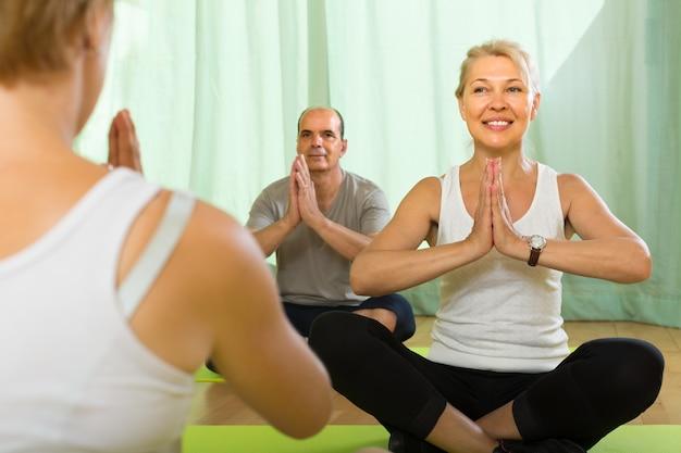 Casal maduro praticando yoga com instrutor