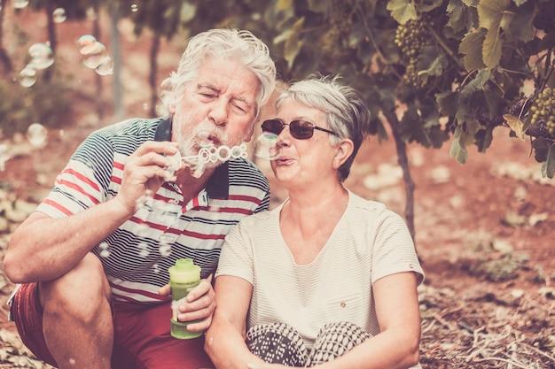 Casal maduro sênior, caucasiano, bonito, viver junto para sempre e brincar com sabão em pó como crianças no campo