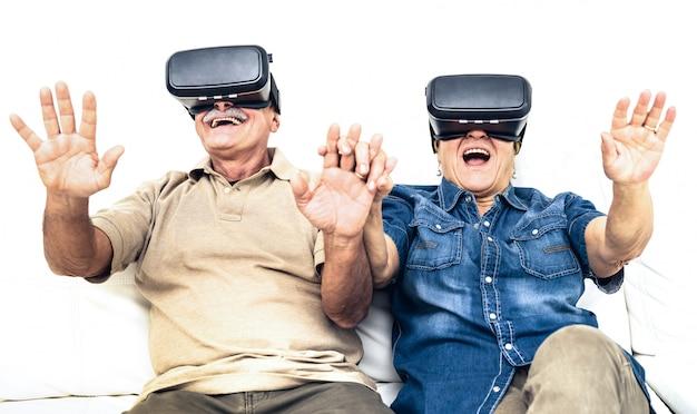 Casal maduro sênior se divertindo junto com o fone de ouvido de realidade virtual, sentado no sofá