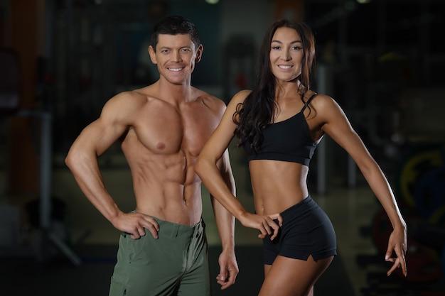 Casal magro em treinamento no ginásio de esporte. estilo de vida ativo, homem musculoso e mulher atraente no clube de fitness