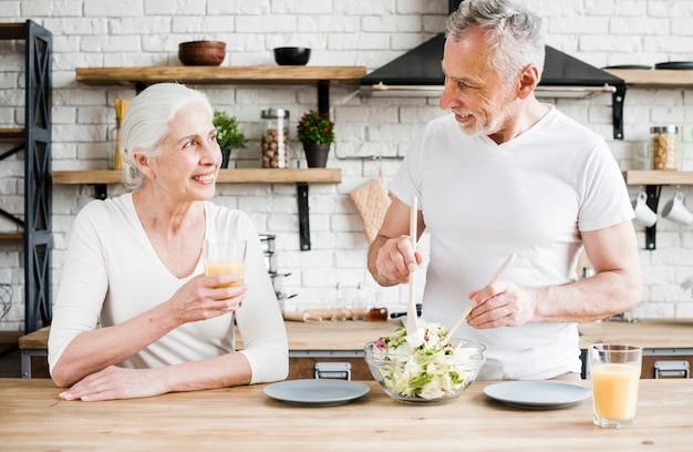 Casal mais velho cozinhando na cozinha