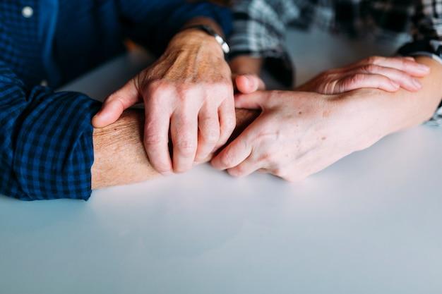 Casal mais velho em lar de idosos de mãos dadas