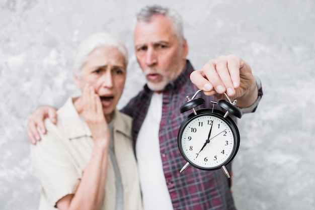 Casal mais velho, segurando um relógio