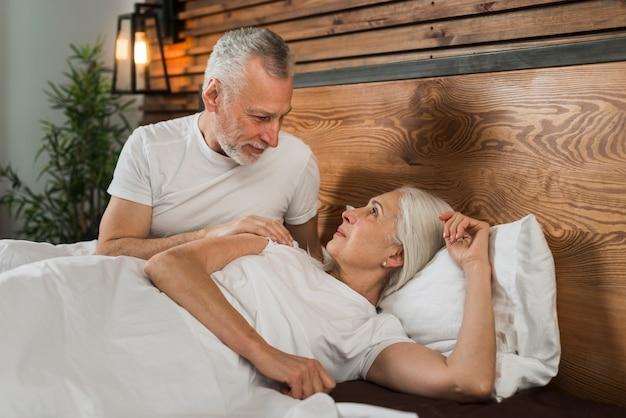 Casal mais velho sentado na cama em casa