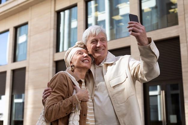 Casal mais velho sorridente ao ar livre tirando uma selfie junto com o smartphone