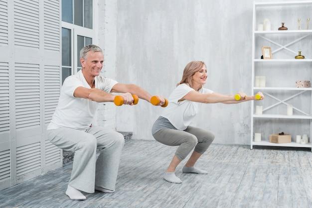 Casal mais velho sorridente, realizando exercícios com halteres em casa