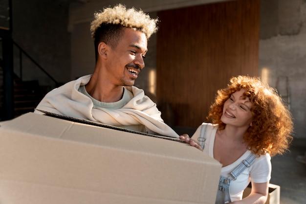 Casal manipulando caixas de papelão com pertences após se mudarem juntos para a nova casa