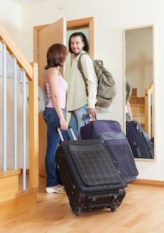 Casal maravilhoso junto com suas bagagens saindo de casa