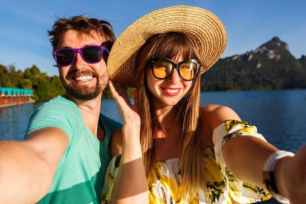 Casal marcando selfie perto da incrível vista do lago e montanhas, vestindo acessórios e roupas elegantes. atmosfera alegre lúdica.