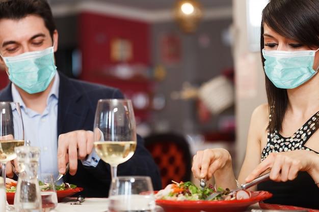 Casal mascarado jantando, conceito engraçado de coronavírus