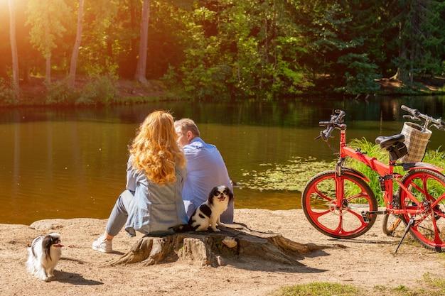 Casal maturo à beira do lago com um cachorro e uma bicicleta sentado ao sol