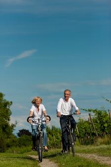 Casal maturo, andar de bicicleta na estrada rural no verão