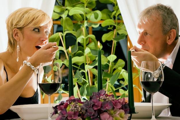 Casal maturo comendo um jantar romântico em um restaurante chique